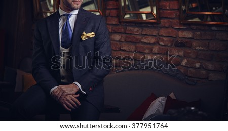 Suited man posing in a bar