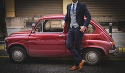 Suited man posing next to a car