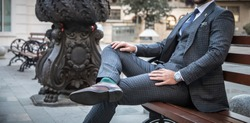Suited man sitting on bench outdoors with his leg crossed and with his hands on his legs