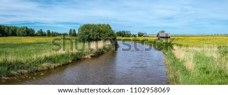 Suitsu, Matsalu National Park, Estonia, Europe 27.05.2018. Panoramic view of river and beautiful yellow flowers on meadow on the sides, beautiful blue sky, small old natural color wooden barns. #1102958069