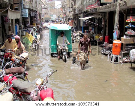 SUKKUR, PAKISTAN - AUG 07:  Peoples pass through rain water that stands at a street after downpour of summer season on August 07, 2012 in Sukkur.