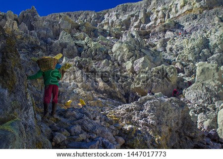 Sulfur miner with typical 90-kg-load of yellow sulfur in bamboo basket ascending on the top of Mount Ijen in Banyuwangi, East Java, Indonesia. Sulfur mining industry in the crater of an active volcano