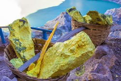 Sulfur mining industry in the crater of a volcano Kawah Ijen, East Java, Indonesia.  A typical 90-kg-load of yellow sulfur in bamboo basket which is usually carried by a single sulfur miner