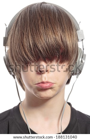 sulking cute teenager boy with hair over his eyes and headphones.