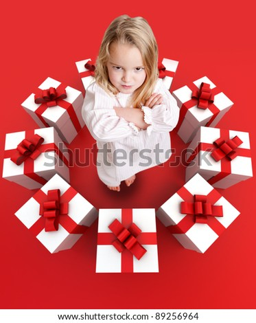 Sulking funny little girl in pajamas surrounded by a ring of presents