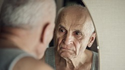 Sullen aged gray haired man looks with sad in mirror in his face reflection