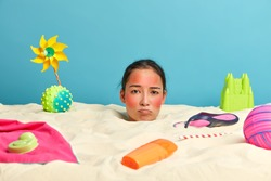 Sullen discontent woman poses in sand over sea background, gets sunbathing during summer day, has red skin on face, bottle of sunscreen, flip flops, toys on coastline. People and vacation concept