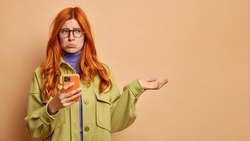 Sullen displeased redhead woman purses lips with gloomy face expression holds mobile phone and raises palm over blank space cannot download application. People bad emotions technology concept
