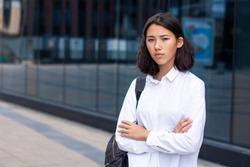 Sullen serious upset asian businesswoman or young Korean or Chinese student university girl in white formal shirt holding her hands or arms crossed and looking straight at camera outdoor office centre