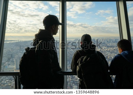 SUMIDA, TOKYO - 19, December, 2017: Three young boys looking over the breathtaking cityscape from the Tokyo Skytree Observation Deck. Concept of reaching towards goals/dreams. #1359648896