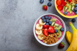 Summer acai smoothie bowls with strawberries, banana, blueberries, kiwi fruit and granola on gray concrete background. Breakfast bowl with fruit and cereal, close-up, top view, space for text