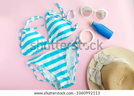 Summer accessories and blue swimming wear bikini, Sunglasses and hat for travelling at beach. Pink pastel colorful background. Fashion and tourism concept
