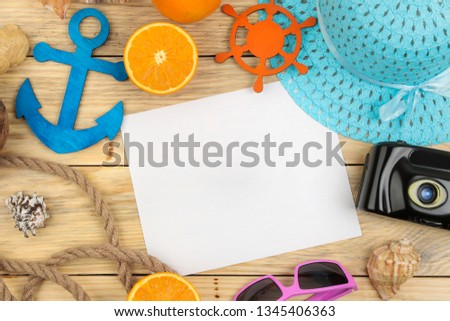 summer accessories. beach accessories. hat, sunscreen, sunglasses, camera, and orange on a natural wooden table. top view. space for text