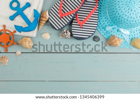 summer accessories. beach accessories. spanking, hat, shells and towel on a blue wooden table. top view. space for text