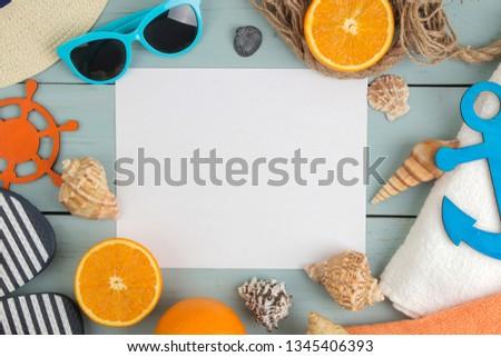 summer accessories. beach accessories. spanking, hat, shells, towel, and sunglasses on a blue wooden table. top view. space for text