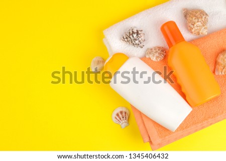 summer accessories. beach accessories. sunscreen and towels on a bright yellow background. top view. space for text