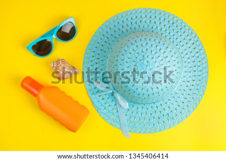 summer accessories. beach accessories. sunscreen, hat and glasses on a bright yellow background. top view.