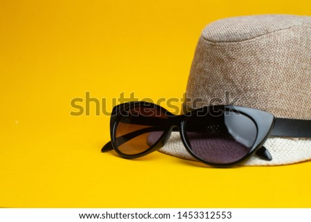 Summer accessories, hat and sun glasses on yellow background. Summer vacation and sea concept. Copyspace for text.