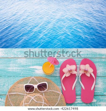 200d9587d Summer accessories on boards near the sea. Flip-flops on beach. Tropical  flower
