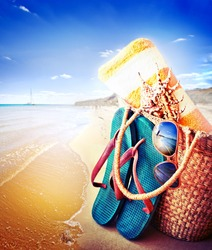 Summer accessories, swimsuit, sun glasses, bag and flip-flops. Closeup of summer beach bag and straw hat on sandy beach.