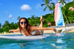 Summer Adventure. Water Sports. Happy Carefree Sexy Woman In Bikini Surfing, Lying On Paddle, Surf Board In Sea At Exotic Resort. Holidays Travel Vacation. Healthy Active Lifestyle. Leisure Activity.