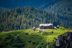 Summer aerial panorama view of Hofpurglhutte - Hofpurgl Alpine Mountain House Hut with forest and alpine mountain range in background. Gosauseen Gosausee lake Salzkammergut  Upper Austria Dachstein