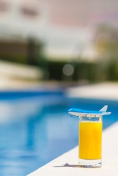 Summer and traveling concept: small airplane model and glass of orange juice near pool