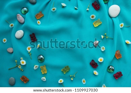 Summer aqua background with copy space. Camomiles, peebles and teddy bears gums in a circle #1109927030