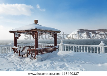 Summer arbour on the shore of lake Baikal at the source of the river Angara, a winter landscape, Siberia, Russia
