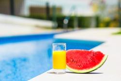 Summer around us: red ripe slice watermelon and glass of orange juice near pool