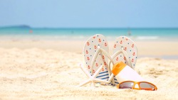 Summer assessorieses. Planing to travel with sunblock and sandal on the beautiful beach and blue sky background. Tropical fashion. Summer Fashion on holiday concept.