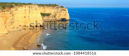 Summer Atlantic rocky coast view with sandy beach Praia da Afurada (Lagoa, Algarve, Portugal). Two shots stitch high-resolution panorama.