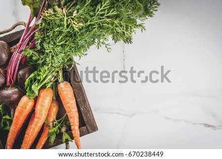 Summer, autumn harvest. Fresh organic farm vegetables in a wooden box on a white marble table - beets, carrots, parsley, tomatoes. Copy space top view #670238449