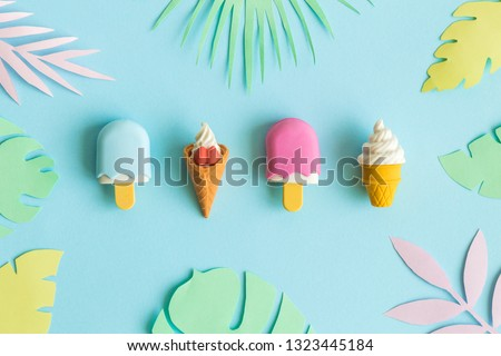 Summer background made of ice cream miniatures and colorful paper tropical leaves minimal creative concept.