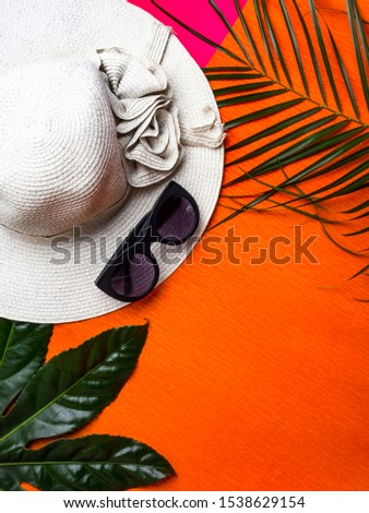 Summer background. Vacation, holiday, travel, tourism concept. Hat, modern sunglasses, tropical palm leaves on orange background. Top view. Copy space #1538629154