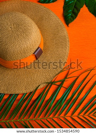 Summer background. Vacation, holiday, travel, tourism concept. Hat, tropical palm leaves on orange background. Top view. Copy space #1534854590