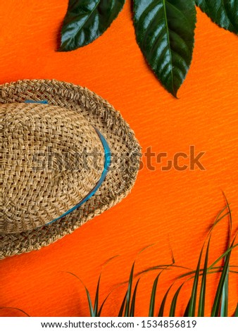 Summer background. Vacation, holiday, travel, tourism concept. Hat, tropical palm leaves on orange background. Top view. Copy space #1534856819