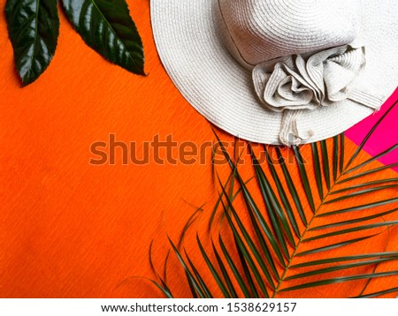 Summer background. Vacation, holiday, travel, tourism concept. Hat, tropical palm leaves on orange background. Top view. Copy space #1538629157