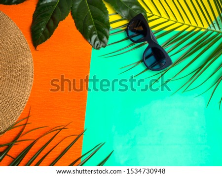 Summer background. Vacation, holiday, travel, tourism concept. Hat, tropical palm leaves on trendy green mint, orange color background. Top view with space for text. #1534730948