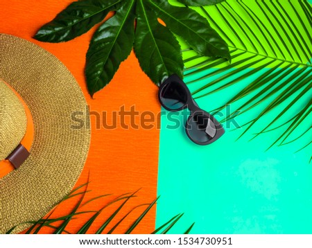 Summer background. Vacation, holiday, travel, tourism concept. Hat, tropical palm leaves on trendy green mint, orange color background. Top view with space for text. #1534730951