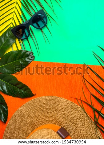 Summer background. Vacation, holiday, travel, tourism concept. Hat, tropical palm leaves on trendy green mint, orange color background. Top view with space for text. #1534730954