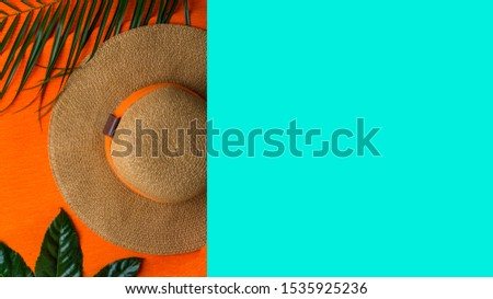 Summer background. Vacation, holiday, travel, tourism concept. Hat, tropical palm leaves on trendy color background. Top view with space for text. #1535925236