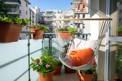 summer balcony with hammock and flowering plants