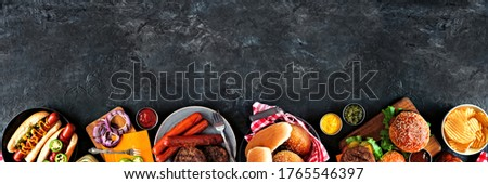 Summer BBQ food table scene with hot dog and hamburger buffet. Overhead view bottom border over a dark slate background. Copy space.