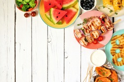 Summer BBQ or picnic food corner border. Selection of grilled meat, fruits, salad and potatoes. Above view over a white wood background. Copy space.