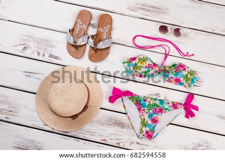 Summer beach accessories, wooden background. Woven hat, slippers, sunglasses, swimsuit in flowery ornament. #682594558
