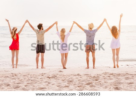 Summer beach at sunset. A group of five people holding hands and raises his arms to the sky. There are two young men and two young women during a day of rest in the sea with deserted beach