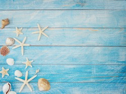 Summer beach background frame, seashells, starfish on light blue background. Top view, space for text.