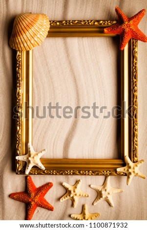 Summer beach background - golden picture frame, shell and starfish on sand