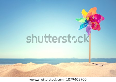 Photo of  Summer beach background, pinwheel or windmill in the sand concept for vacation copy or message